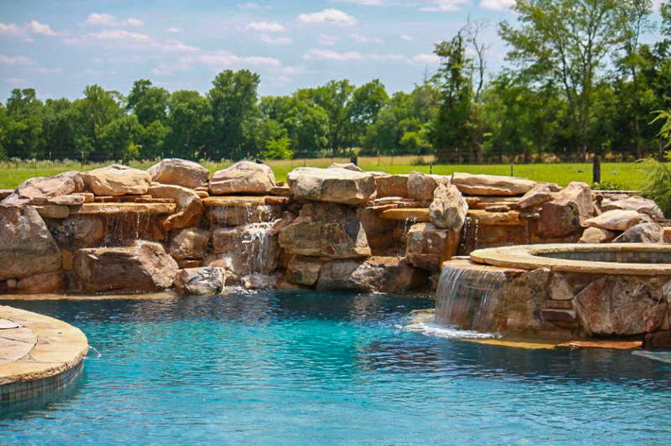 Luxury stone work and water feature spilling into In-ground pools and spas in Nashville, Franklin, Clarksville TN